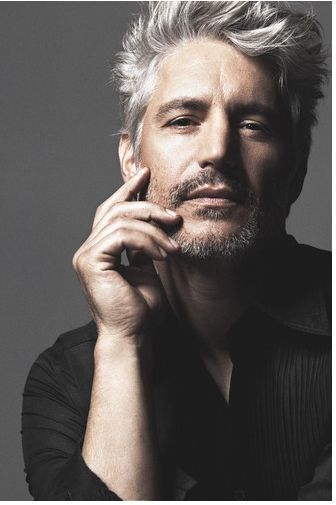 head shot grey color hair man with with his hand on his face