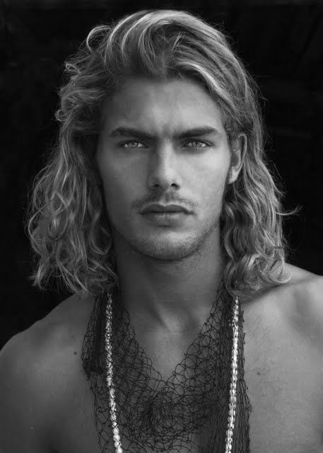 head shot of a man with long hair